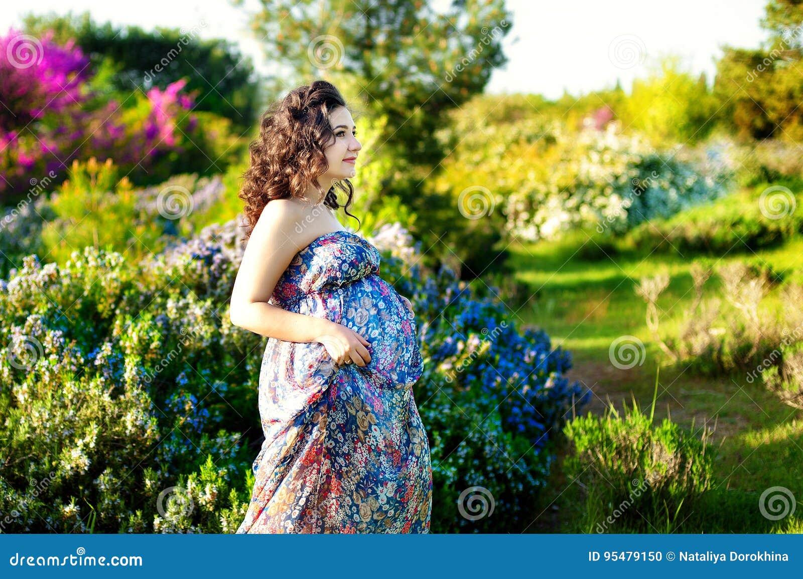 Ładny kobieta w ciąży pozuje w zielonym rozmarynie uprawia ogródek