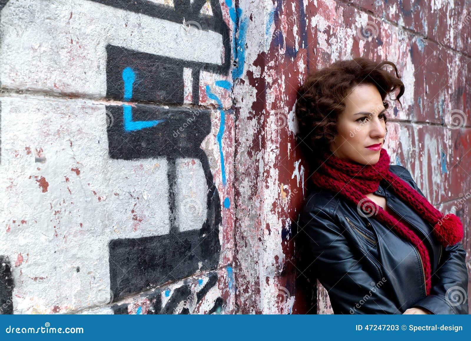 Ładny kobiety czekanie przy graffiti ścianą