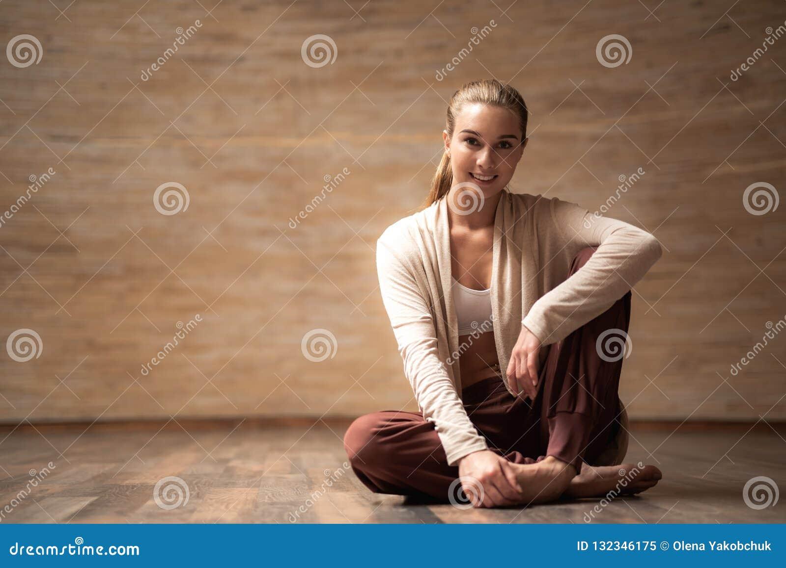 Ładny młodej damy obsiadanie na ono uśmiecha się i podłodze