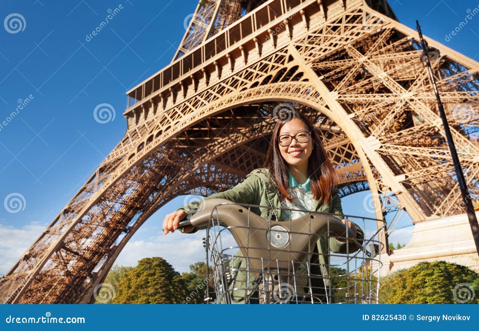 Ładny młodej kobiety jazdy rower blisko wieży eifla