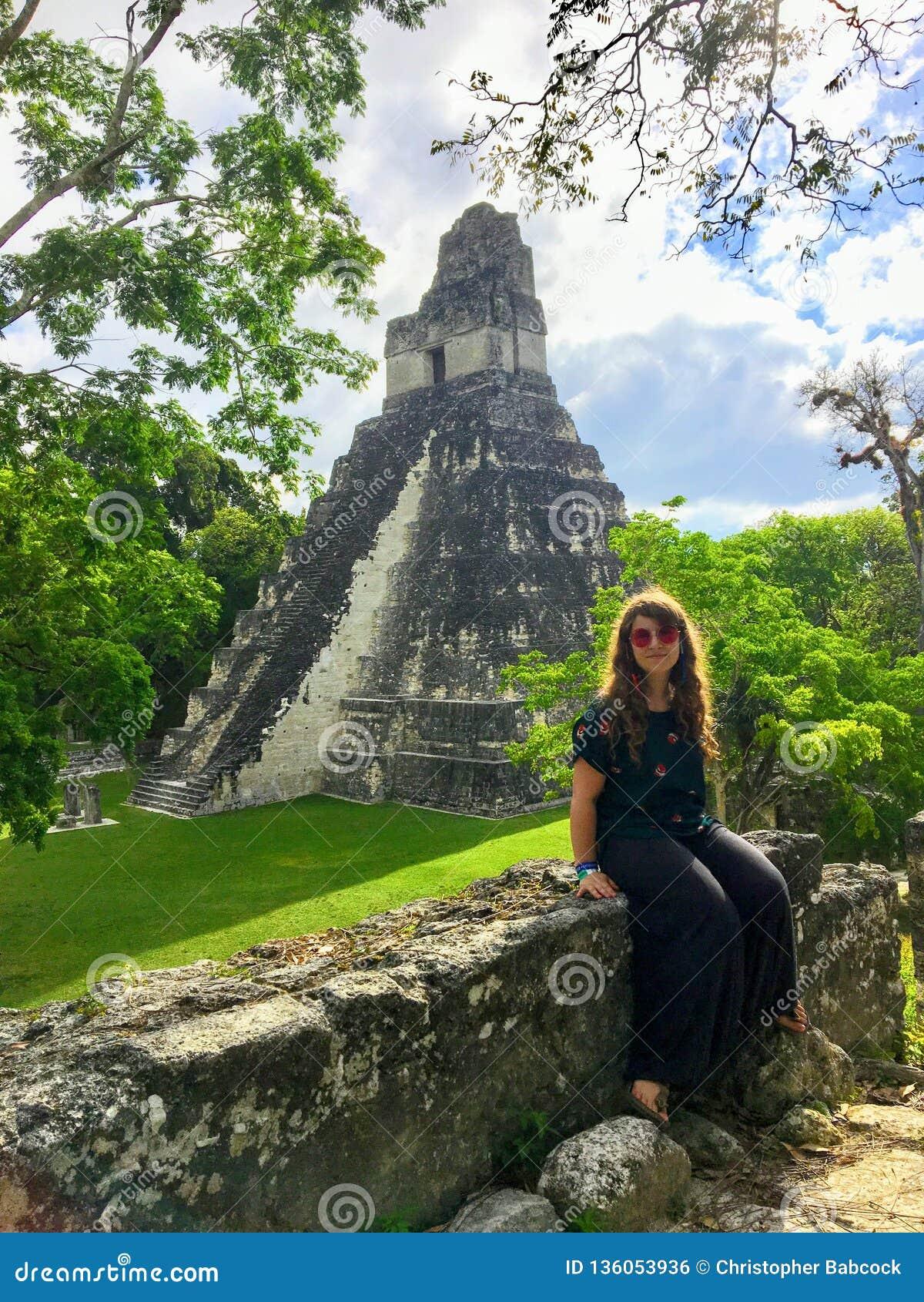 Ładny młody żeński turysta pozuje przed Tikal ruinami, antyczne Majskie ruiny w tropikalnych lasach deszczowych północny Gwatemal