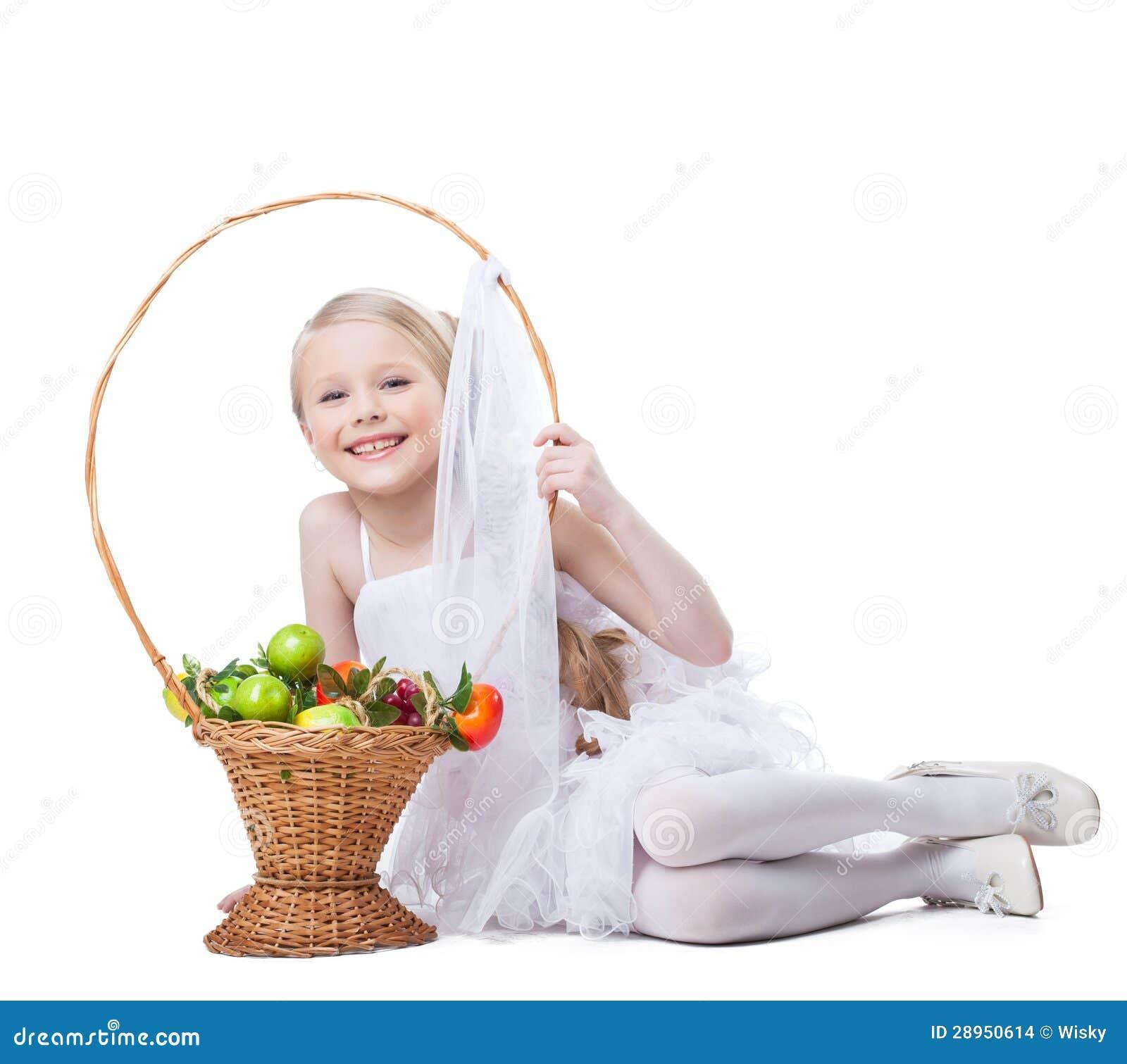 Ładny mała dziewczynka uśmiech z koszem owoc