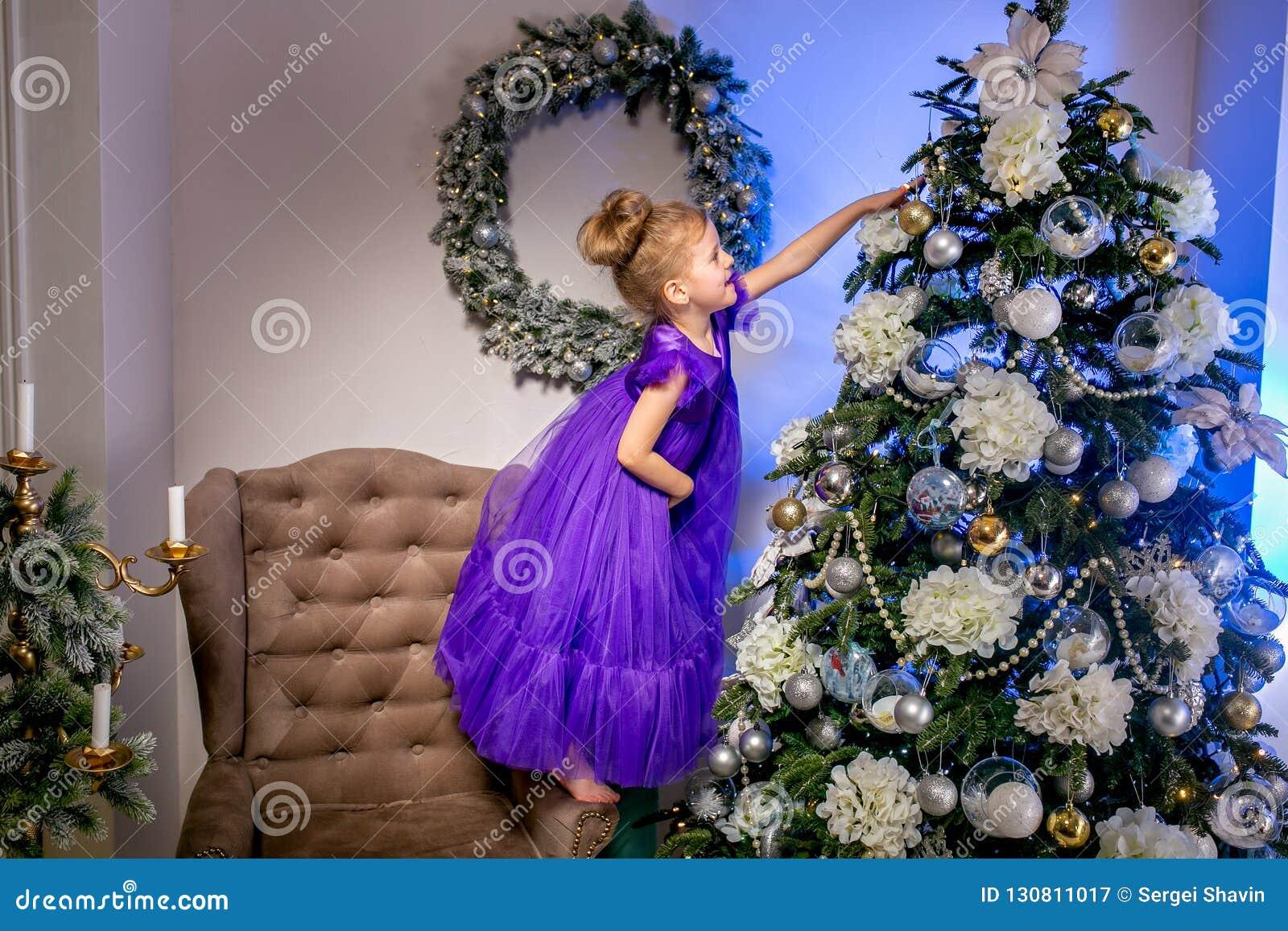 Ładny małej dziewczynki 4 lat w błękitnej sukni Dziecko w Bożenarodzeniowym pokoju z teddybear, dużym zegarem, choinka, brązu kar