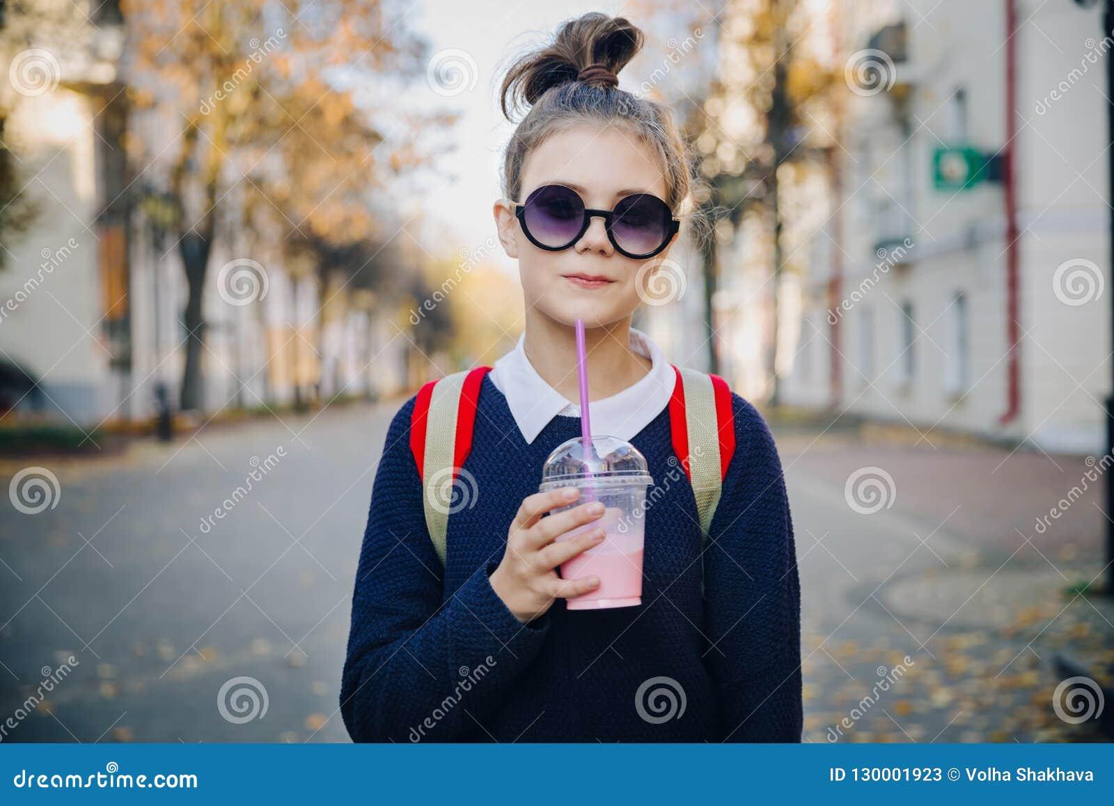 Ładny modniś nastoletni z czerwoną torbą pije milkshake od plastikowej filiżanki chodzącej ulicy między budynkami Śliczna dziewcz
