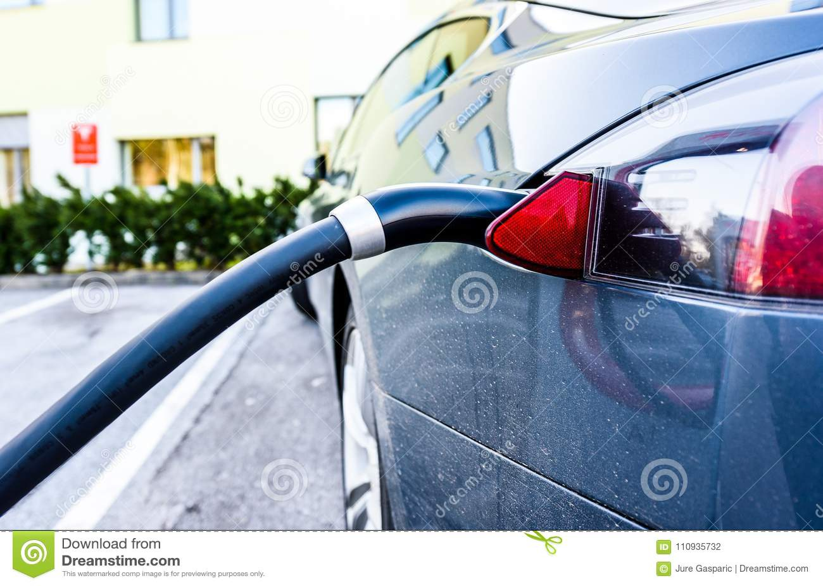Ładuje elektryczny samochód z czernią ładuje elektrycznego kabel czopującego