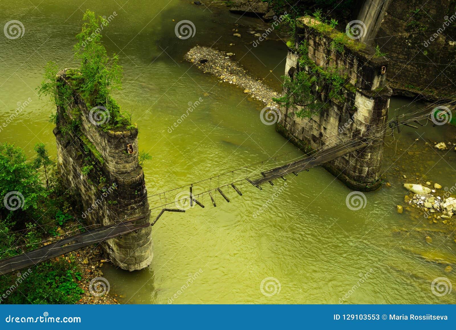 Łamany zwyczajny zawieszenie most przez halną rzekę