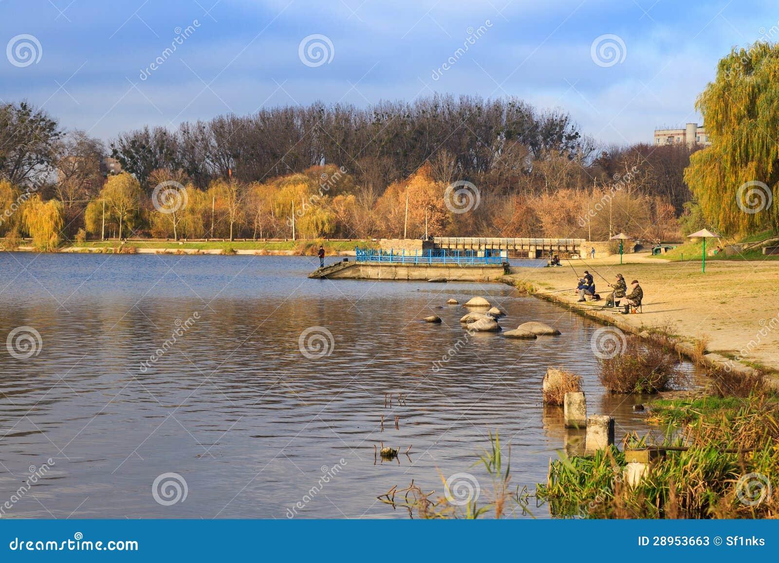 Łapać rybi rybacy na jeziorze w jesieni
