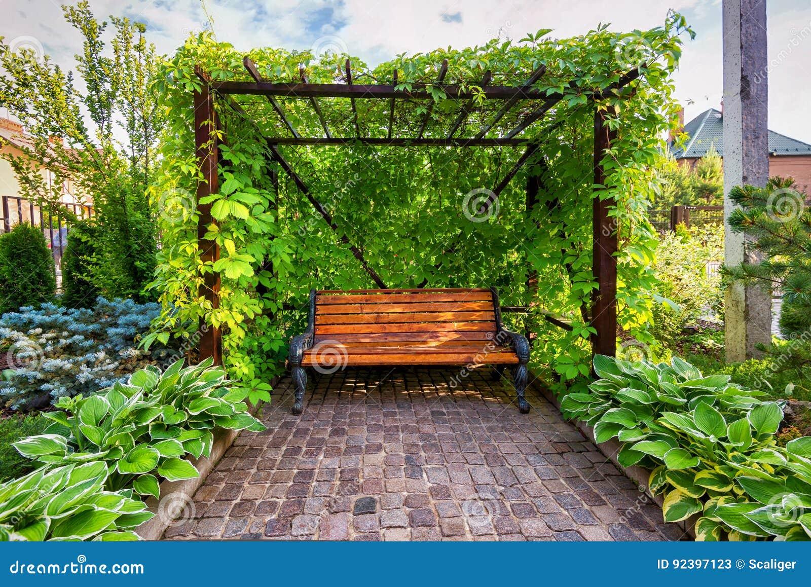 Ławka w dom kształtującym teren ogródzie