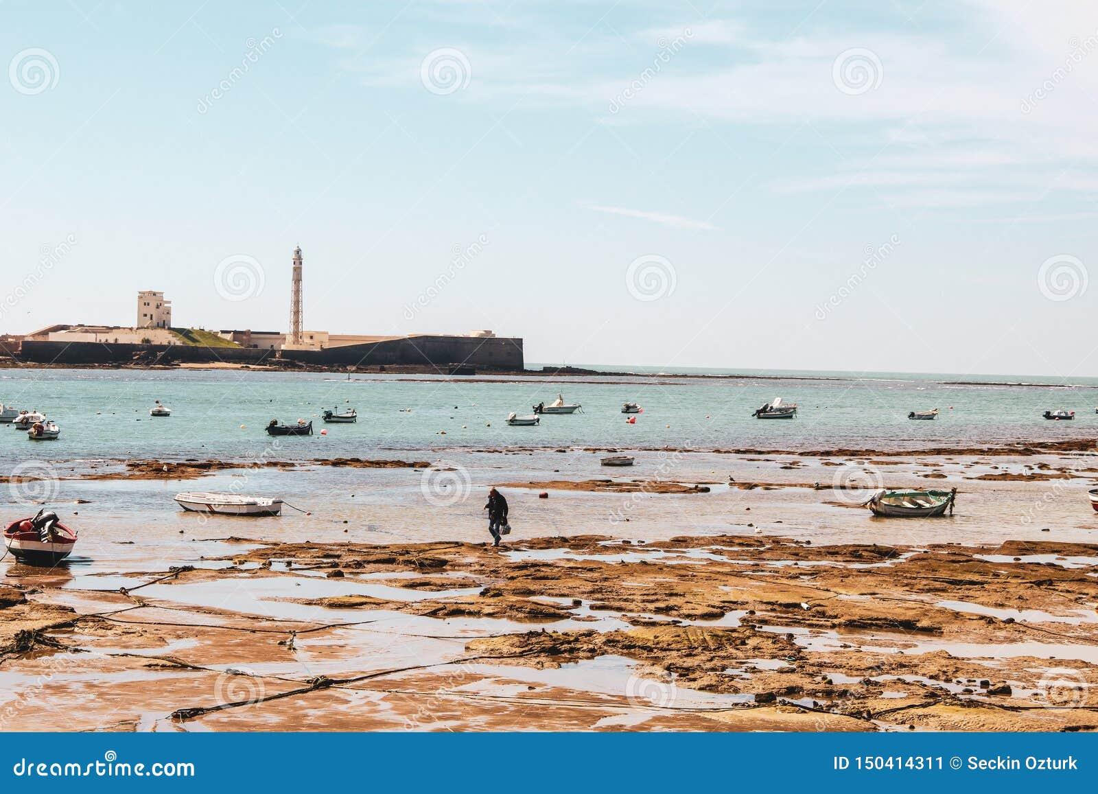 Łodzie i przypływ w plaży Cadiz w Andalusia, Hiszpania