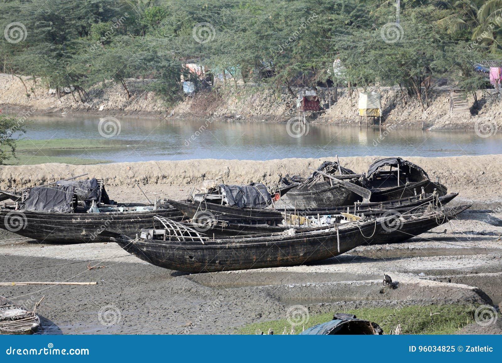 Łodzie rybacy splatali w błocie przy niskim przypływem na rzecznym Malta pobliskim Konserwuje miasteczku, India