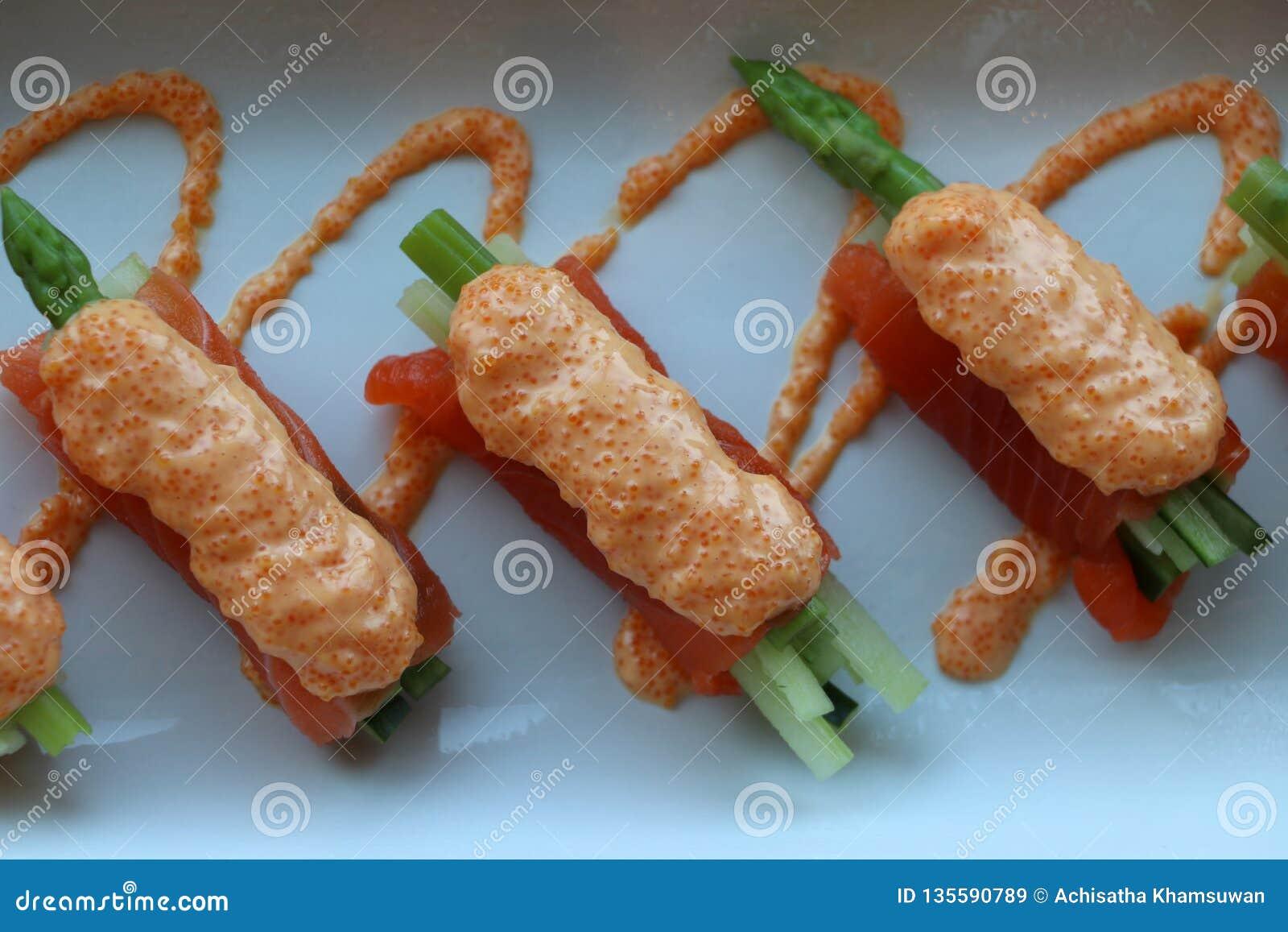 Łososia polędwicowy opakunek na szparagowych warzywach i nalewa z jajkami ryba w białym talerzu