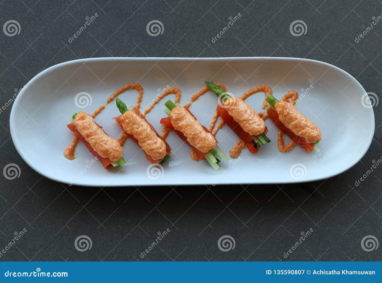 Łososia polędwicowy opakunek na szparagowych warzywach i nalewa z jajkami stawiającymi w białym owalu talerzu ryba
