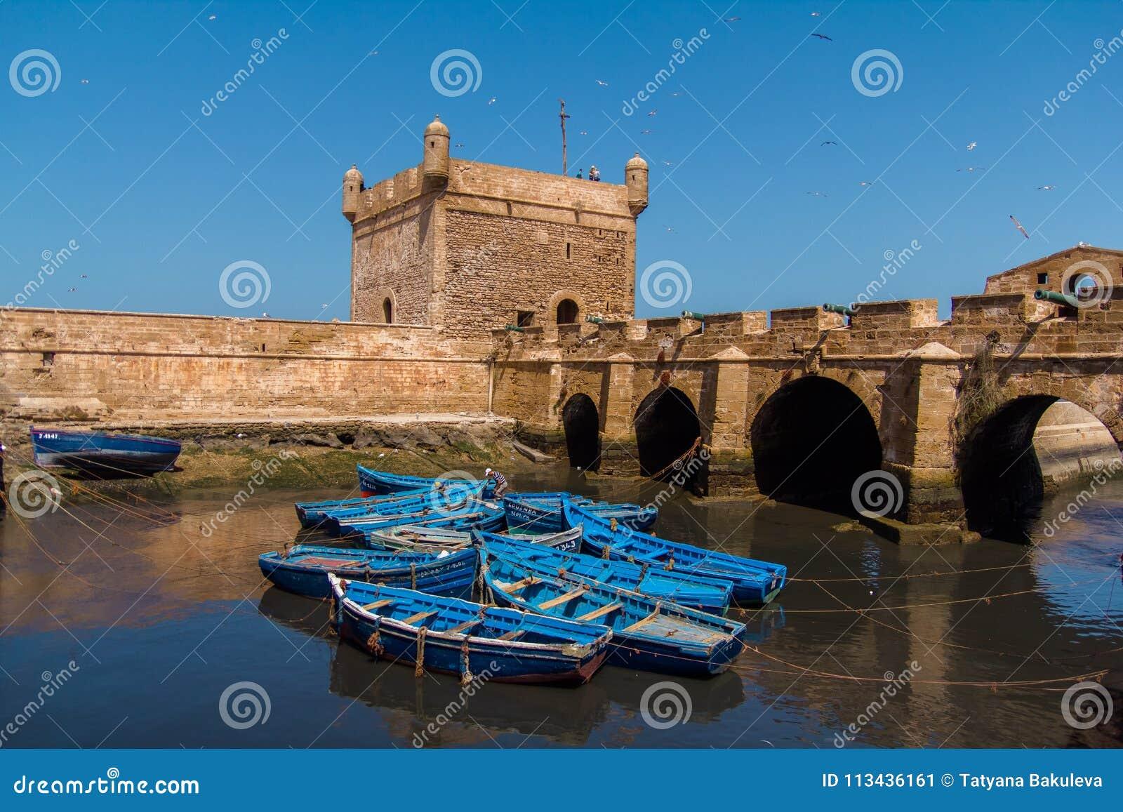 Łowić piękne błękitne łodzie, przekładnię i chwyta na tle Castelo real Mogador w Essaouira starym schronieniu,
