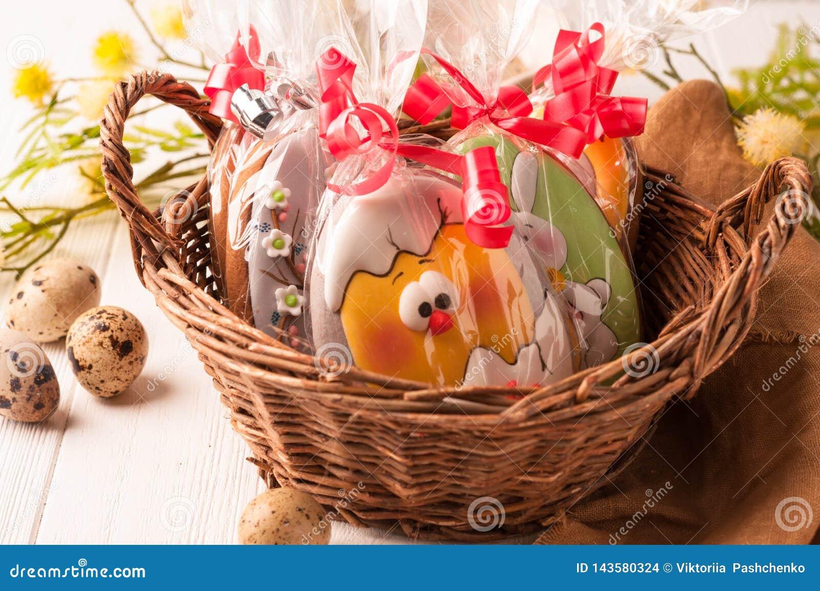 Łozinowy brązu kosz z zawijającymi Easter ciastkami blisko przepiórek jajek i kwitnąć gałąź