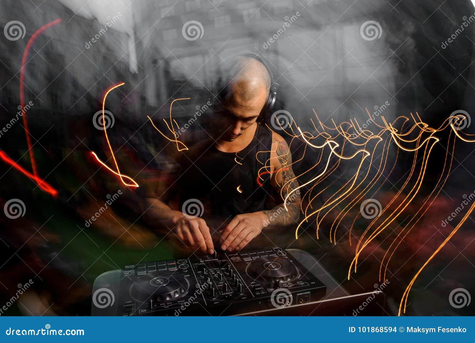 Łysy klub DJ z hełmofon mieszankami muzycznymi