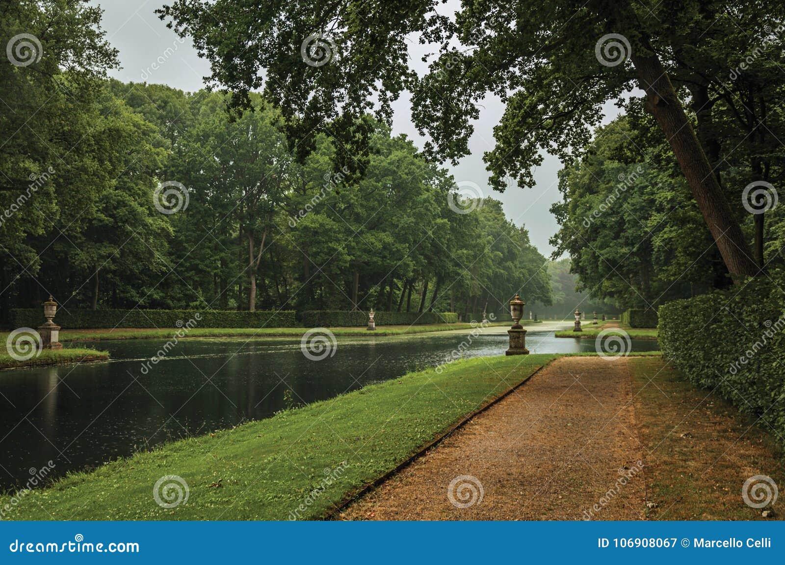 Ścieżka wśród lesistych ogródów i kanał na deszczowym dniu wokoło De Haar Roszujący blisko Utrecht,
