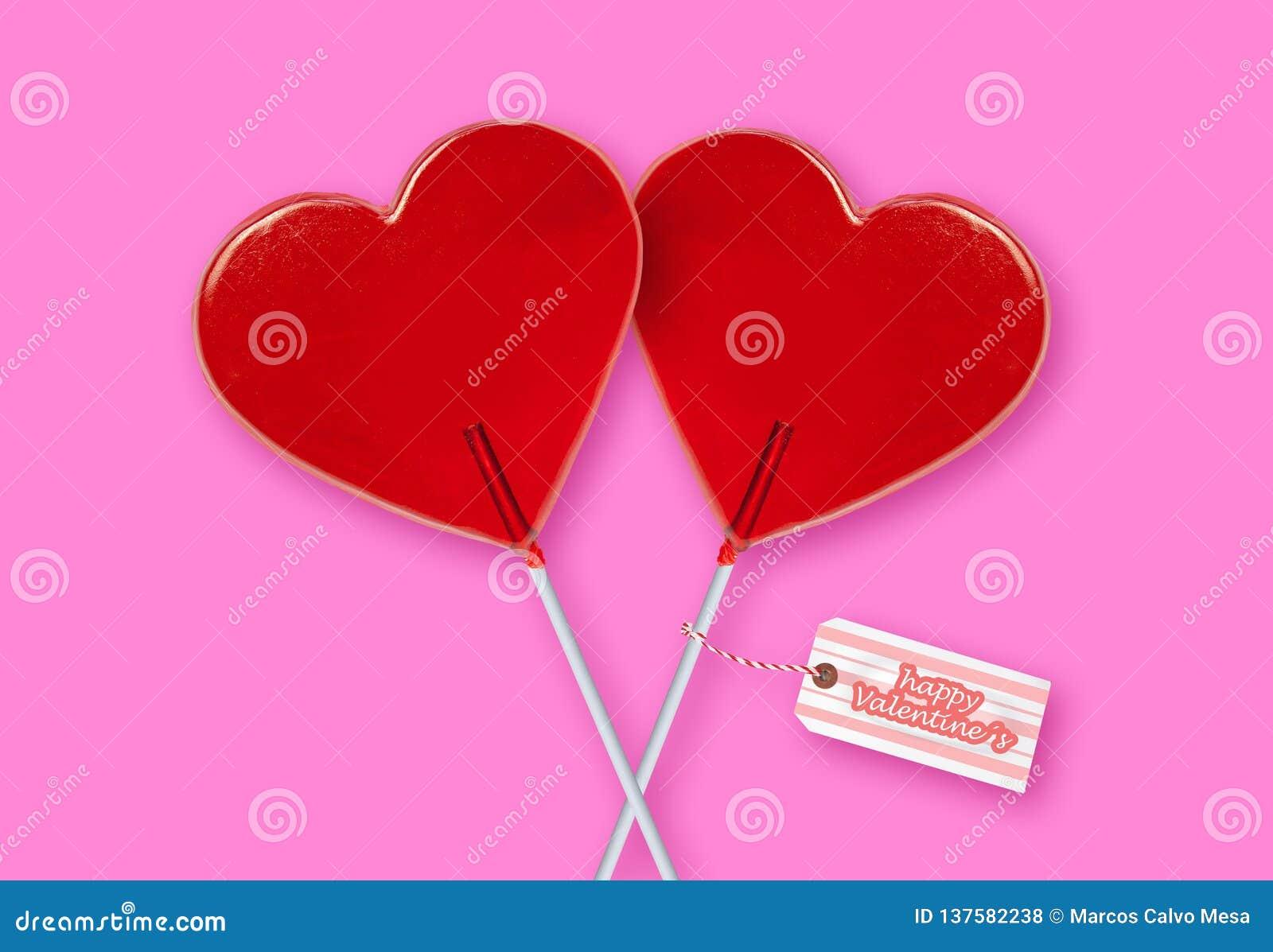 Ściennego papieru walentynek dnia kartka z pozdrowieniami z parą czerwoni kierowi kształtów lizaki wpólnie odizolowywający na róż