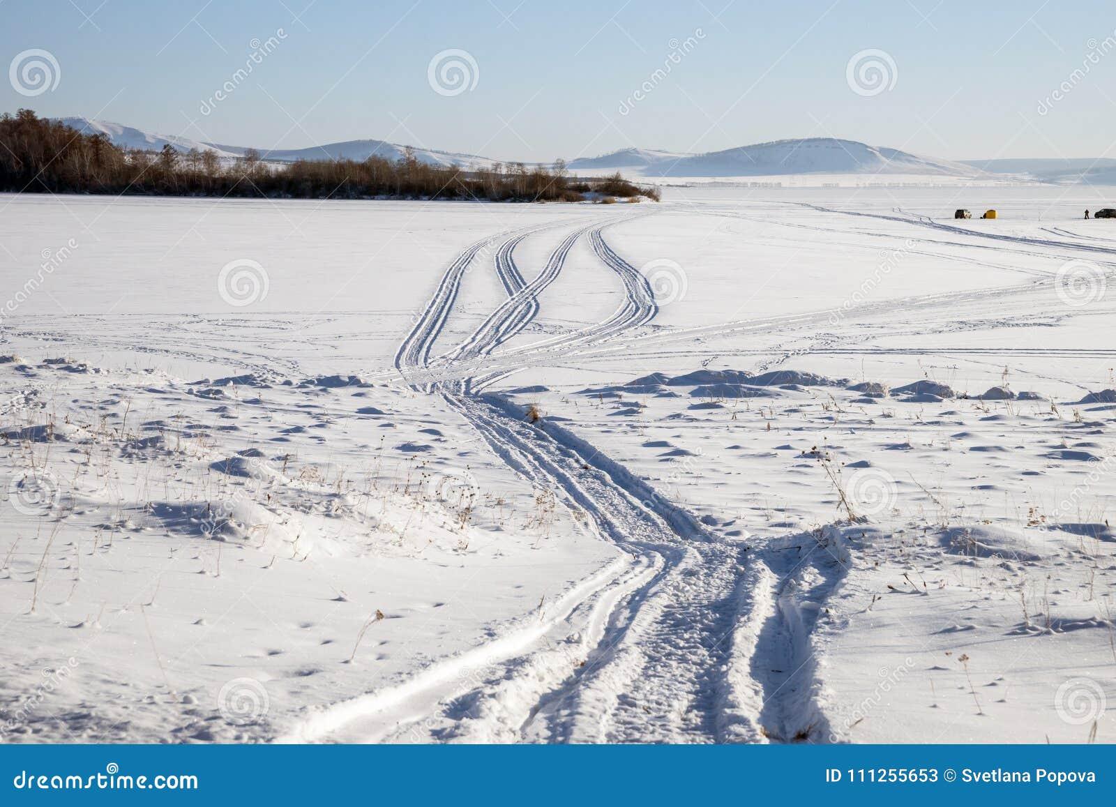 Ślad od snowmobile na śnieżnym jeziorze z rybakami w tle