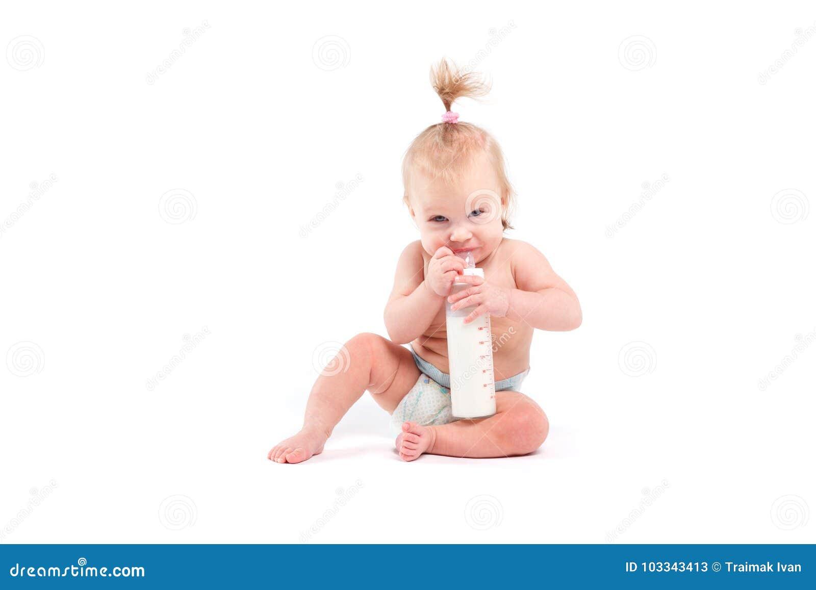 Śliczna ładna dziewczynka w białej pieluszka chwyta butelce