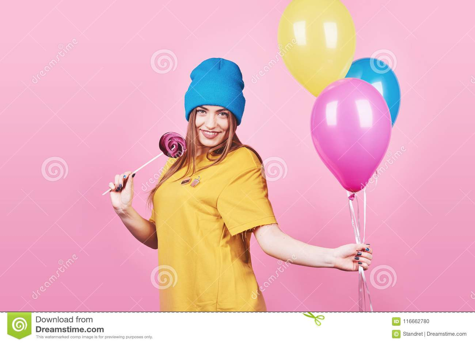 Śliczna śmieszna dziewczyna ono uśmiecha się na różowym tle w błękitnej nakrętki portrecie trzyma lotniczych kolorowych balony i