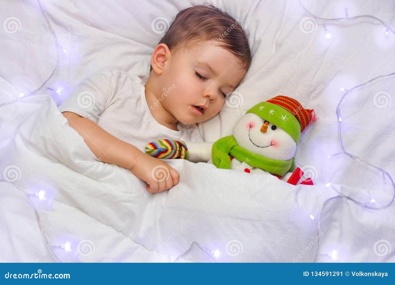 Śliczna berbeć chłopiec śpi na białej pościeli z jego ulubionym zabawkarskim bałwanem w błękitnych światłach girlanda