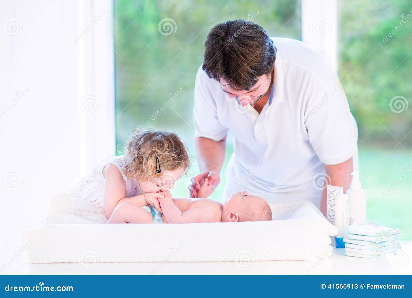 Śliczna berbeć dziewczyna całuje jej nowonarodzonego dziecko brata