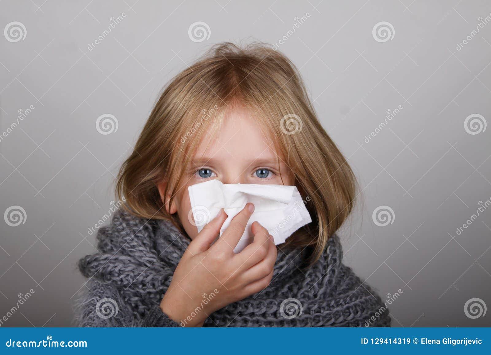 Śliczna blondyn mała dziewczynka dmucha jej nos z papierową tkanką Dziecko zimy alergii opieki zdrowotnej grypowy pojęcie