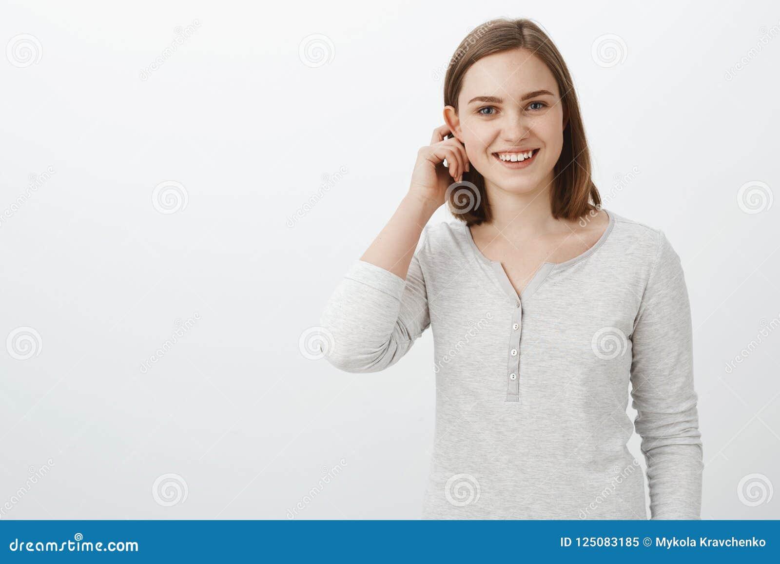 Śliczna budzący emocje nastoletnia dziewczyna w przypadkowej bluzce trzepocze włosy za flapped uszatym i uśmiecha się szeroko czu