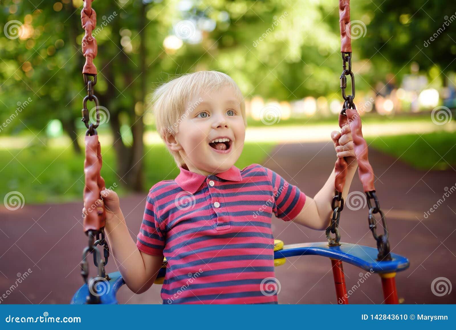 Śliczna chłopiec ma zabawę na plenerowym boisku Dziecko na huśtawce