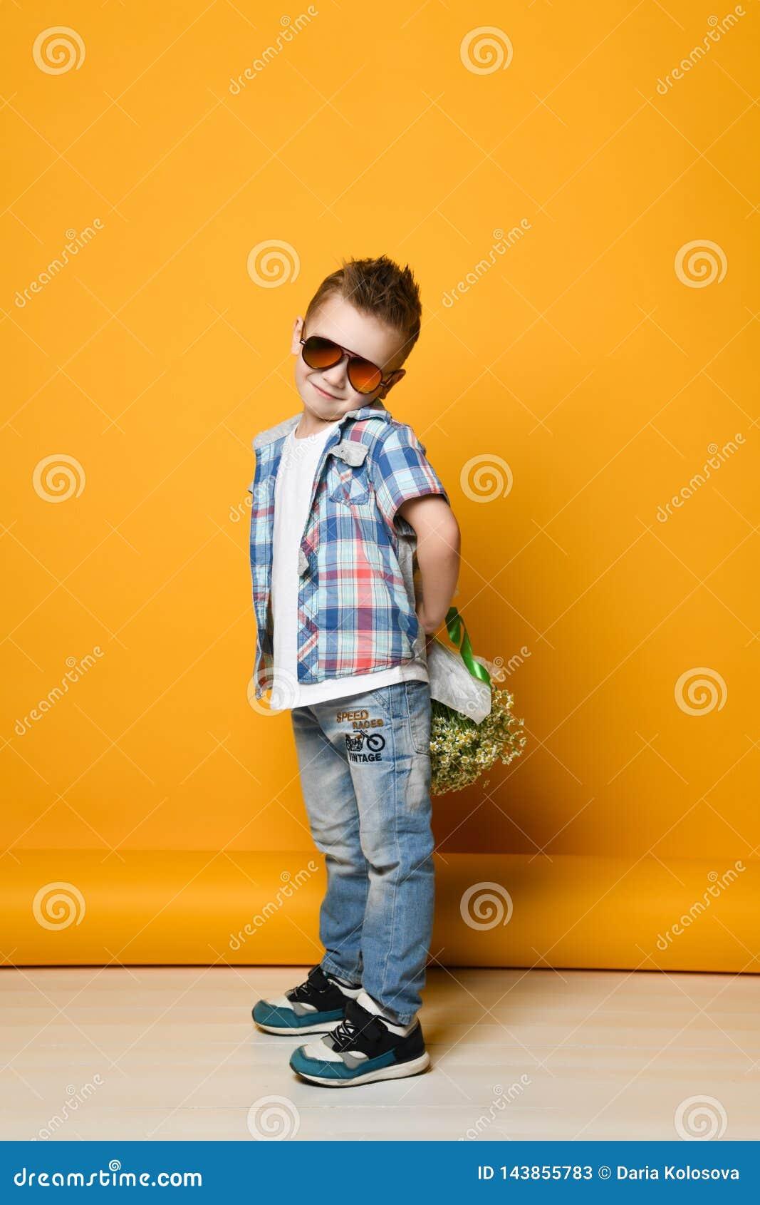 Śliczna chłopiec trzyma bukiet kwiaty