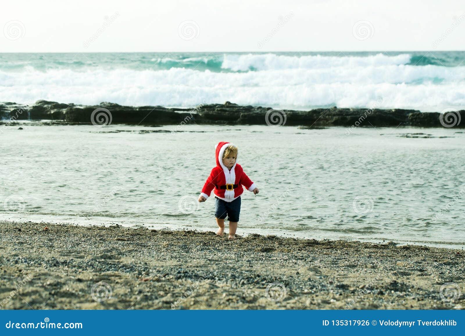 Śliczna chłopiec w czerwonym Santa żakiecie na otoczak plaży