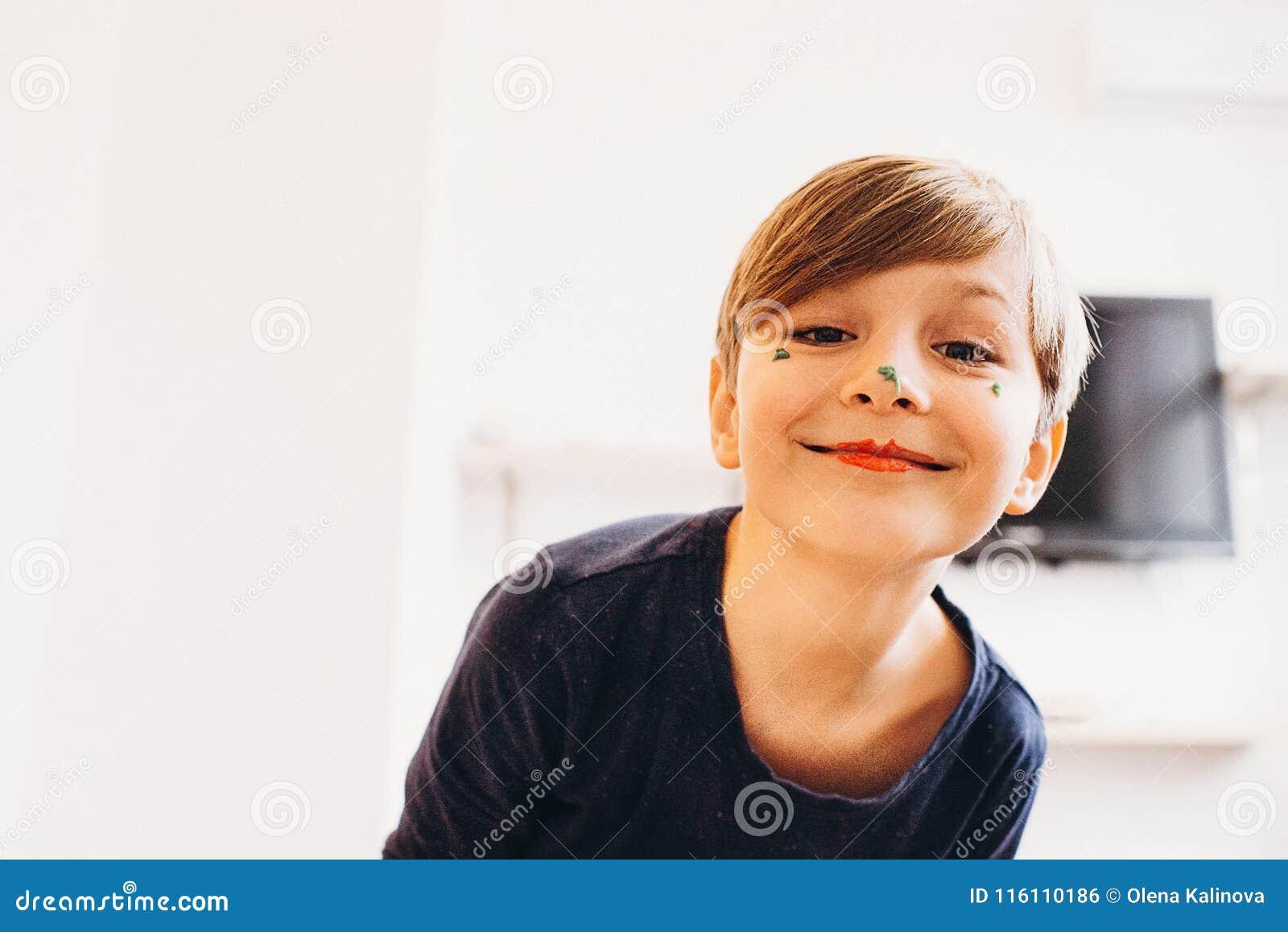 Śliczna chłopiec z twarzą malującą jako błazen, ono uśmiecha się