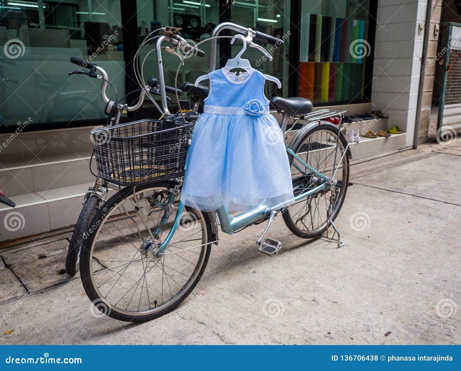 Śliczna dziecko bielu i błękita suknia wiesza na bicyklu