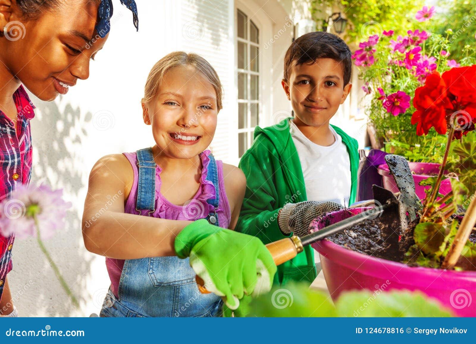 Śliczna dziewczyna pracuje w ogródzie z jej przyjaciółmi