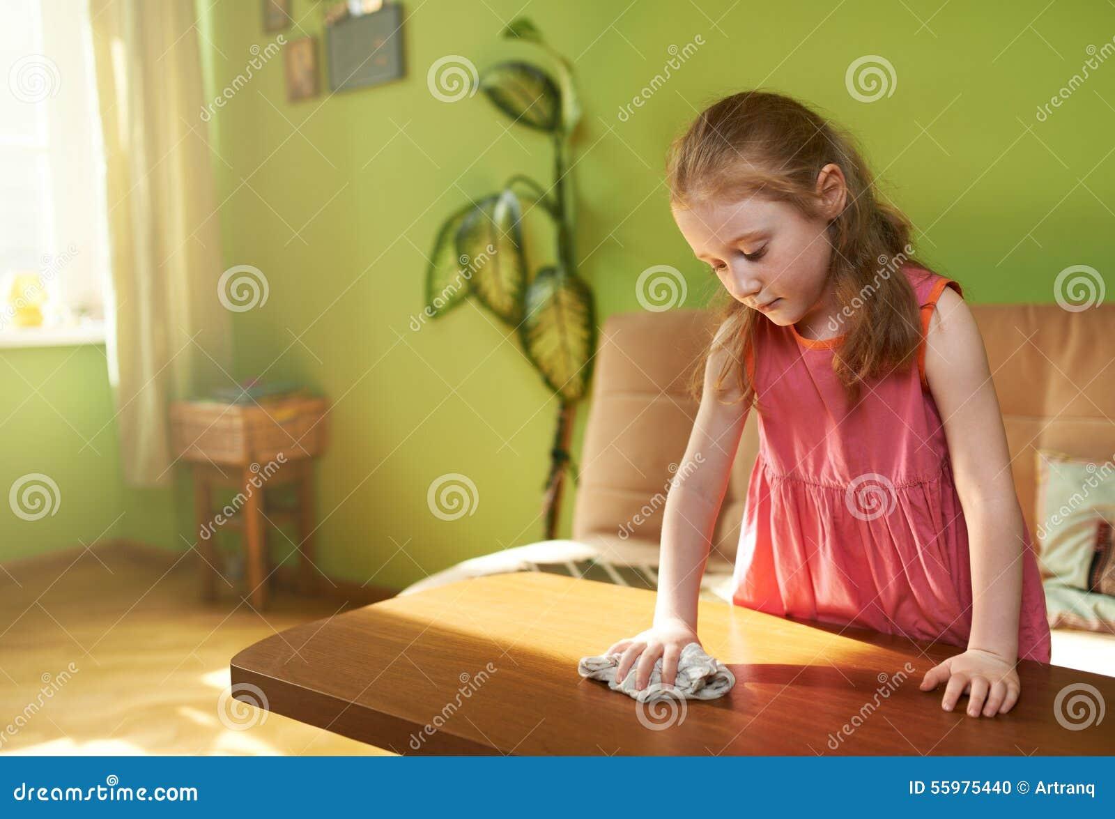 Śliczna dziewczyna wyciera pył na stole