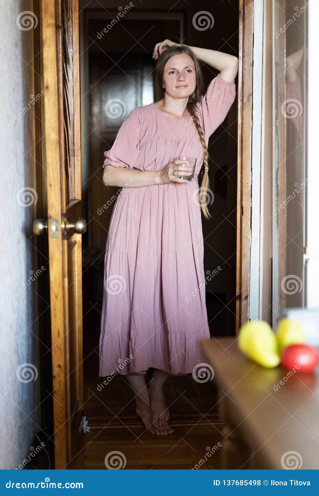 Śliczna europejska dziewczyna w różowej sukni stoi w drzwi i trzyma kubek twarz się portret dziewczyny zaskoczeni young Międzynar