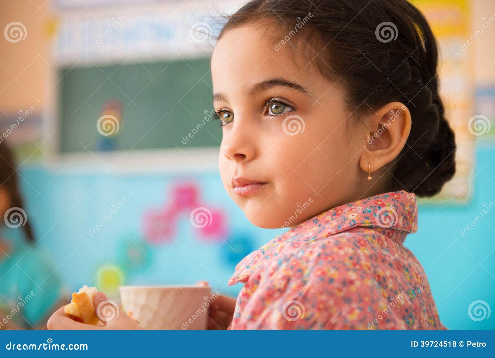 Śliczna latynoska dziewczyna z filiżanką mleko przy daycare