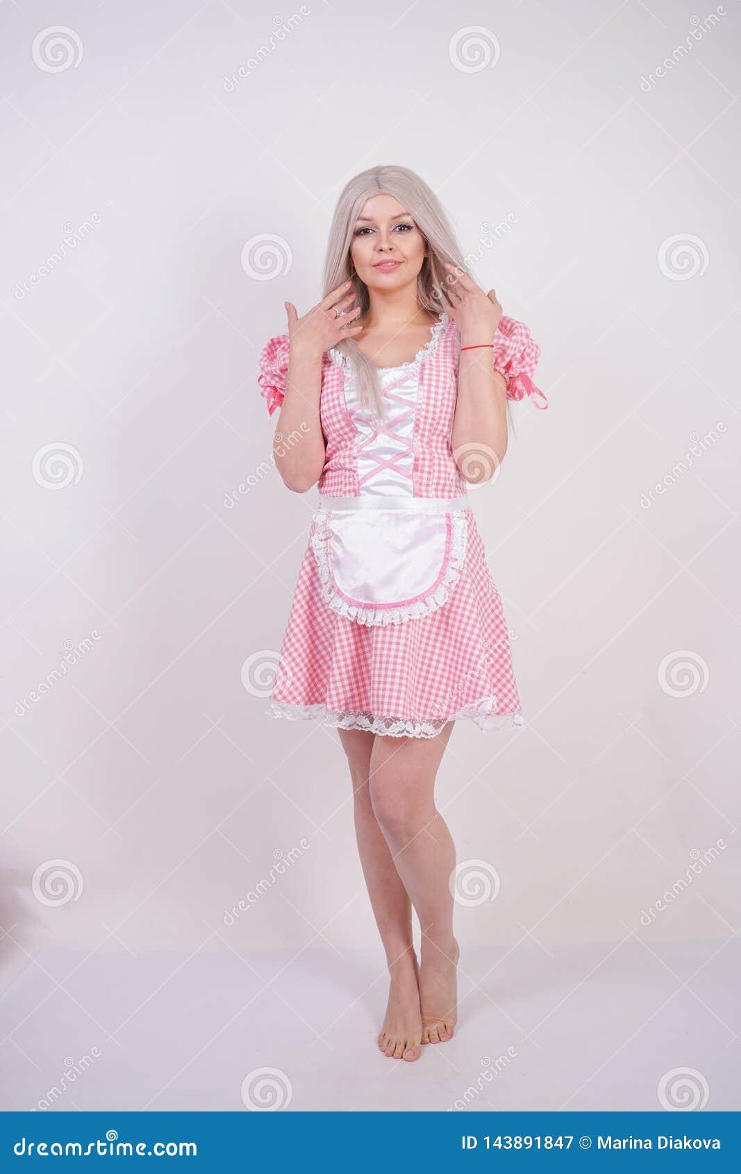 Śliczna młoda caucasian nastoletnia dziewczyna w różowej szkockiej kraty Bawarskiej sukni z fartuchem pozuje na białym Pracownian