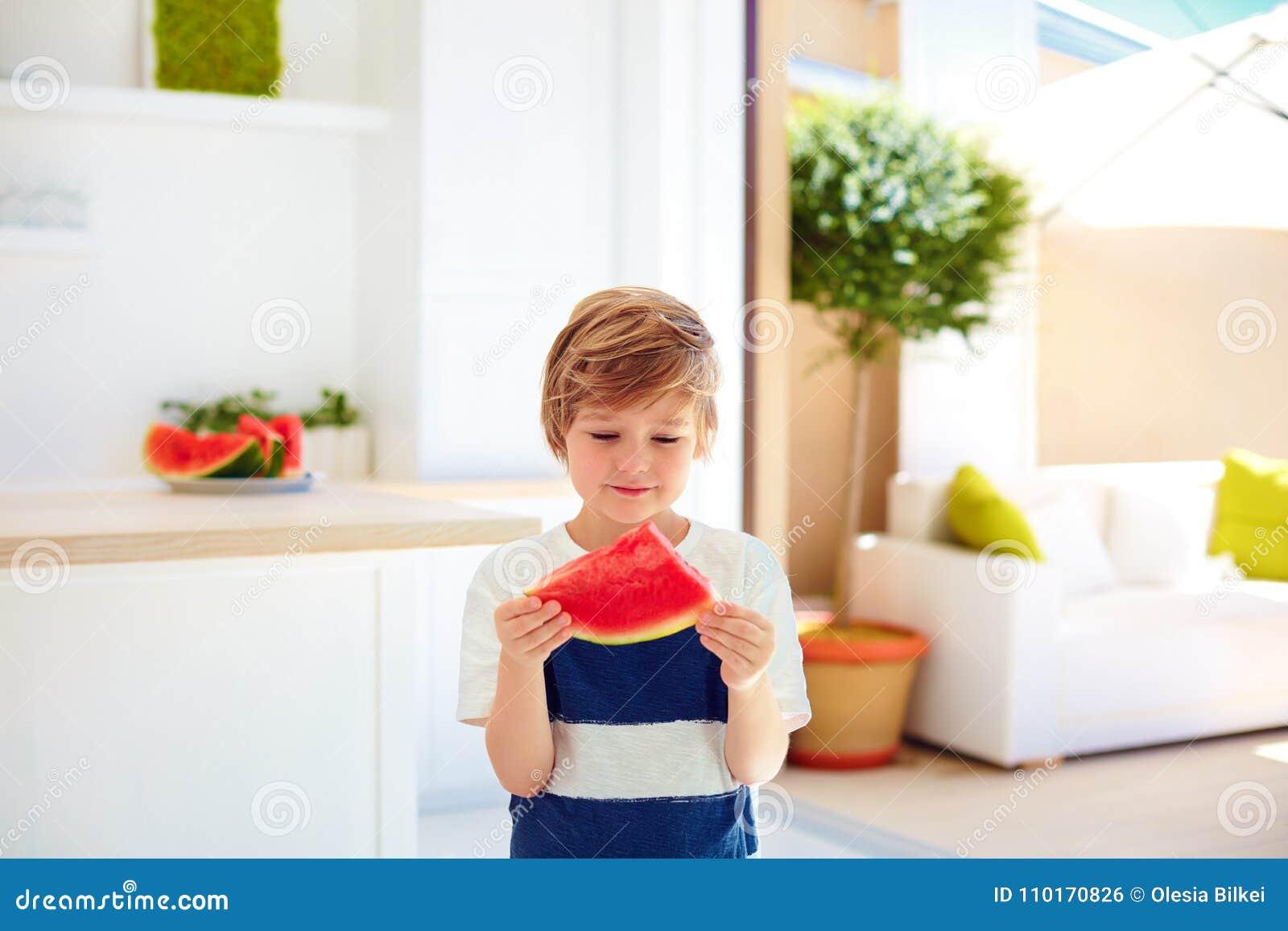 Śliczna młoda chłopiec, dzieciak je kawałek dojrzała arbuz kuchnia w domu