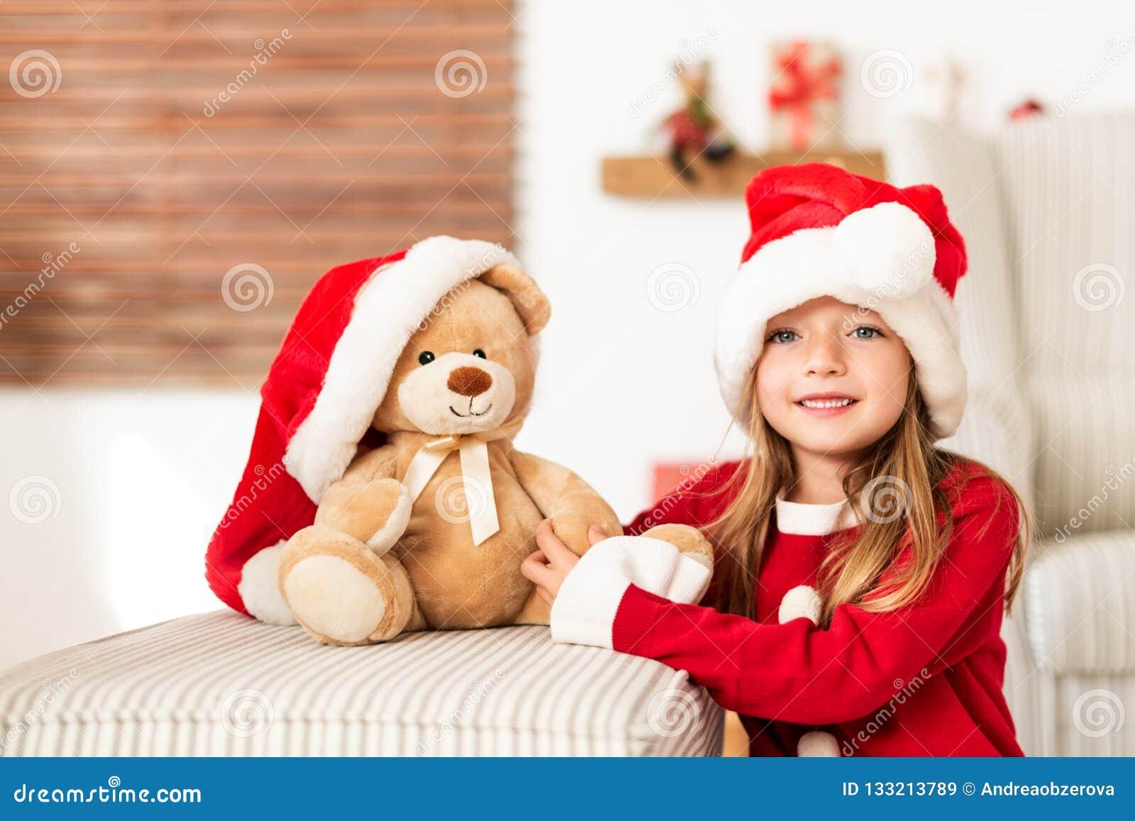 Śliczna młoda dziewczyna jest ubranym Santa kapelusz trzyma jej boże narodzenie teraźniejszość, miękka część zabawkarski miś Szcz