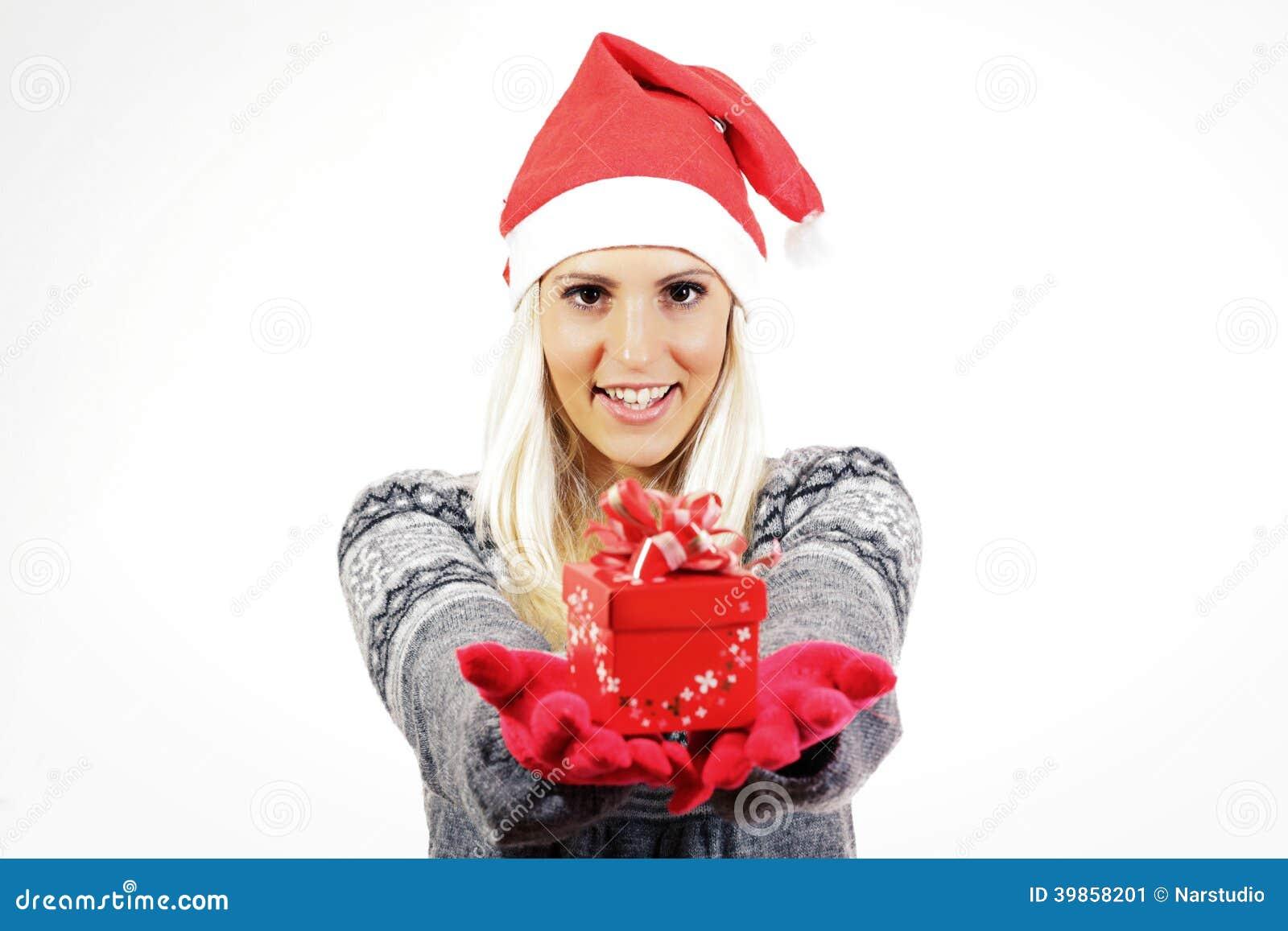 Śliczna młoda dziewczyna z Święty Mikołaj kapeluszem, trzyma teraźniejszość