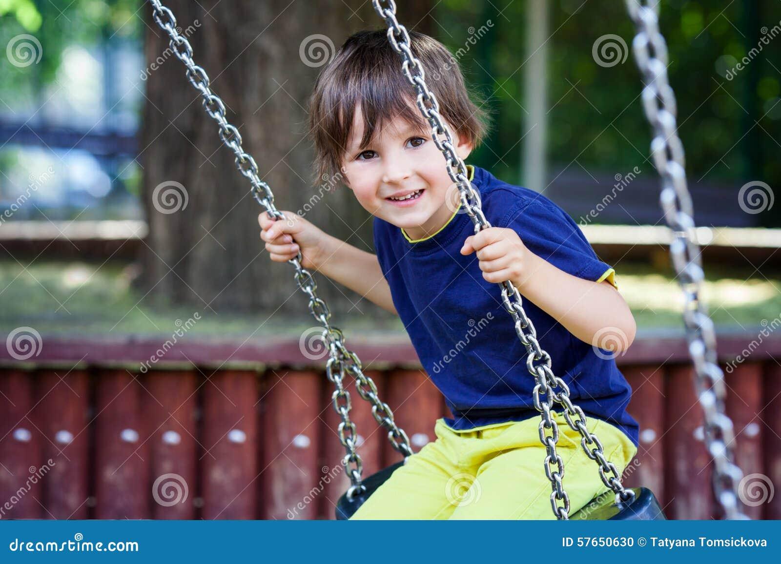 Śliczna mała berbeć chłopiec, huśta się w parku, lato