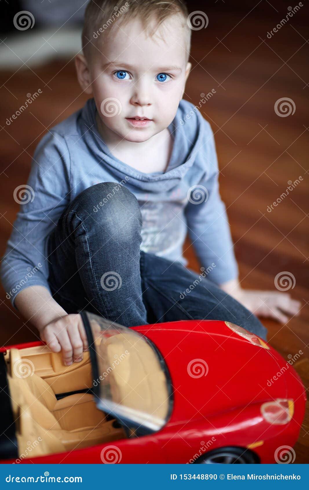 Śliczna mała caucasian chłopiec, blondyn z niebieskimi oczami, sztuki z zabawką - czerwony samochód, siedzi na podłodze Pi?kny dz