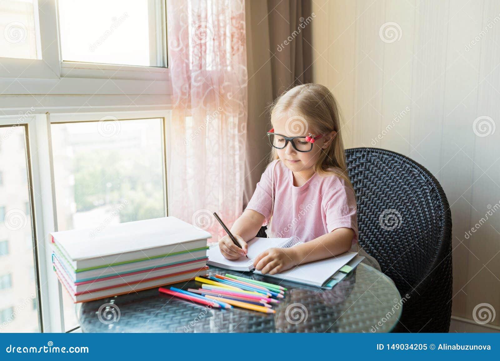 ?liczna ma?a caucasian dziewczyna robi pracie domowej i pisze papierze Dzieciak cieszy si? uczenie z szcz??ciem w domu M?dry, edu