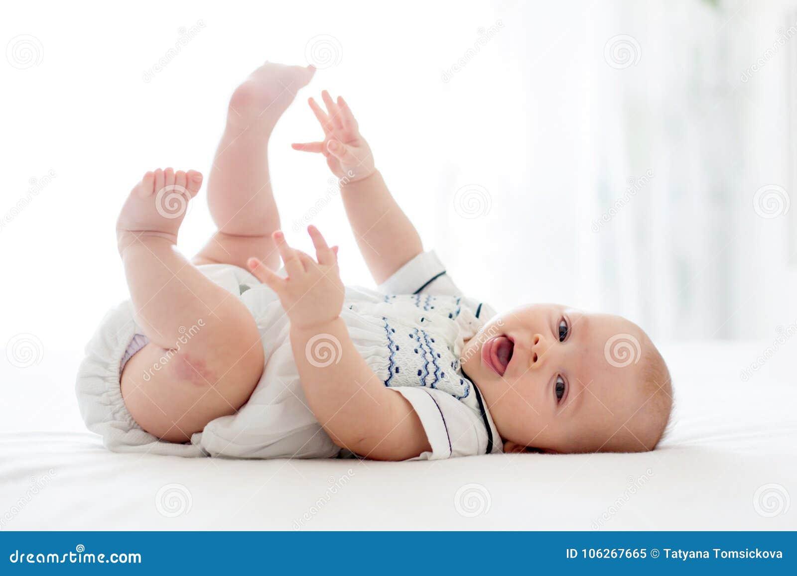 Śliczna mała cztery miesięcy stara chłopiec, bawić się w domu w łóżku