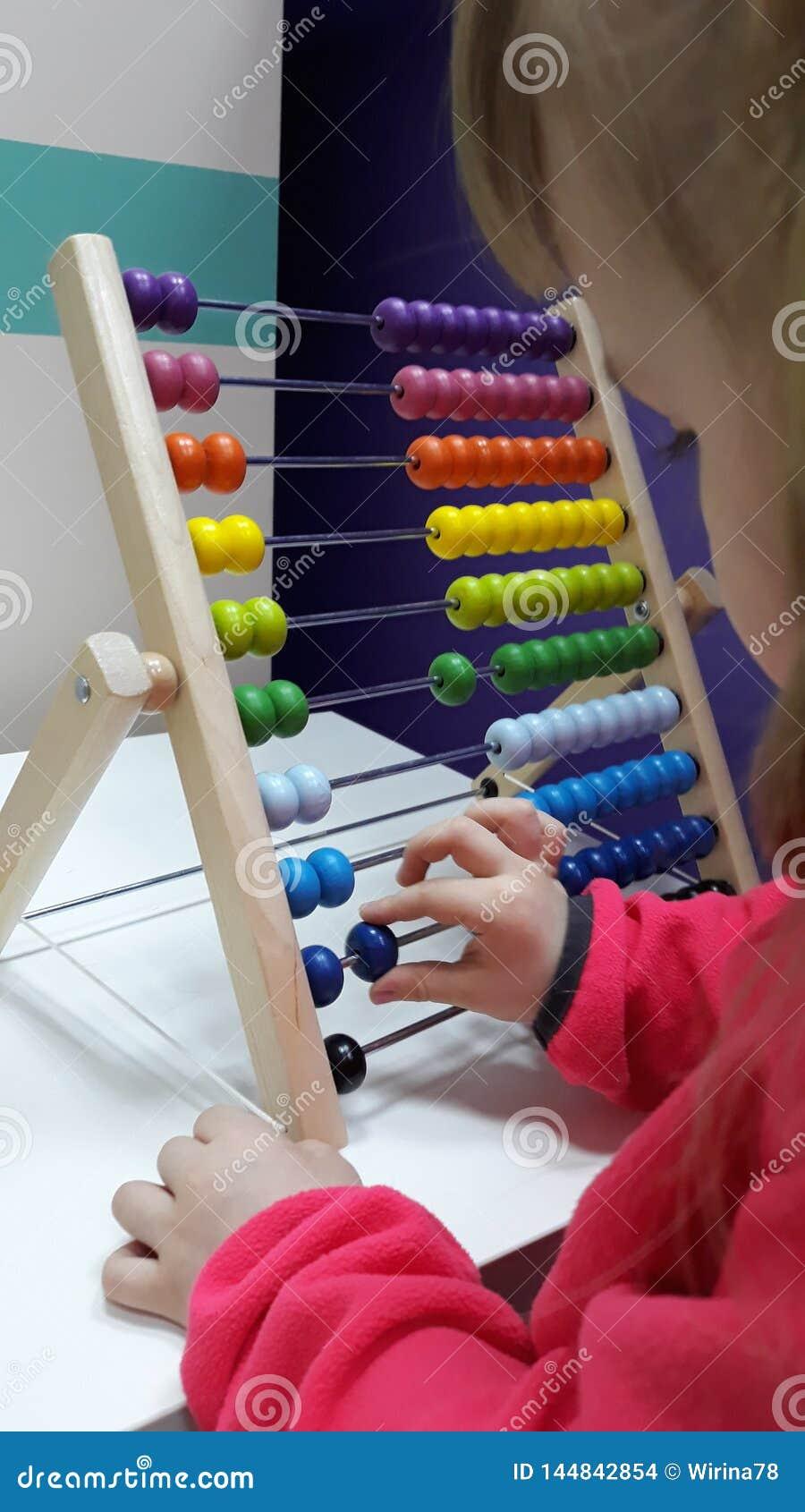 ?liczna ma?a dziewczynka bawi? si? drewnianego abakusa abakusa dziecka odliczaj?ca dziewczyny pomoc M?drze dziecko uczenie liczy?