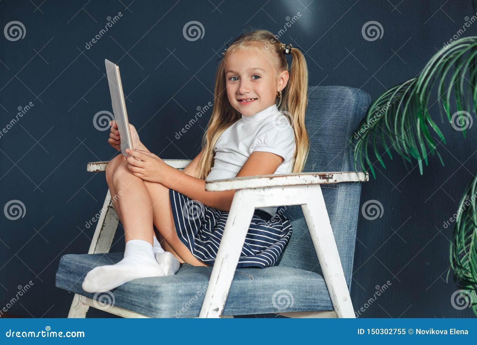 Śliczna mała dziewczynka bawić się z pastylką Szczęśliwa blondy dziewczyna w domu Śmieszna urocza dziewczyna ma zabawę w dzieciak