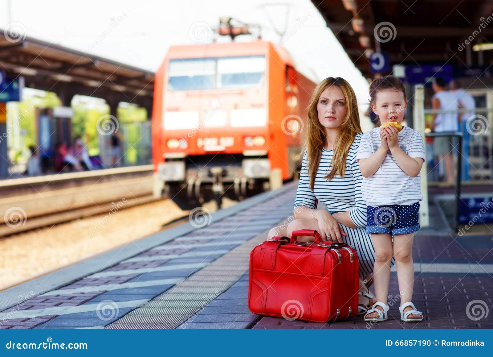 Śliczna mała dziewczynka i matka na staci kolejowej