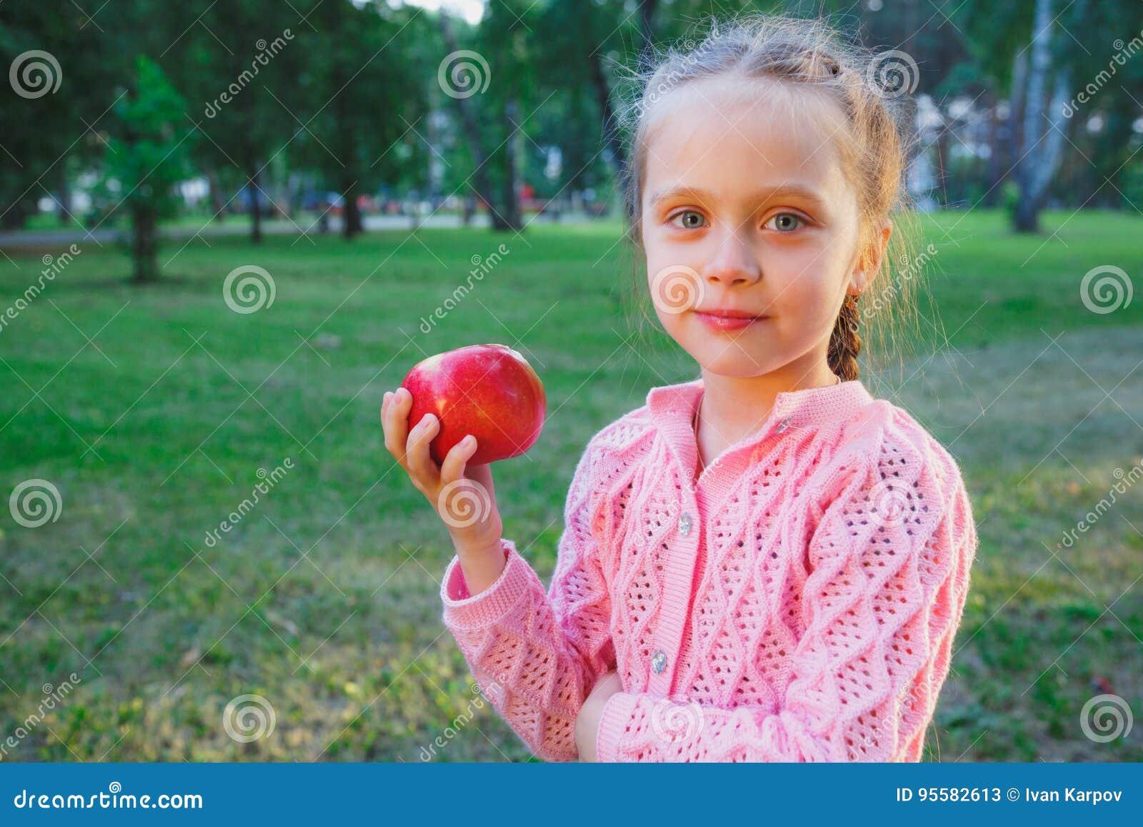 Śliczna mała dziewczynka je czerwień - wyśmienicie jabłko