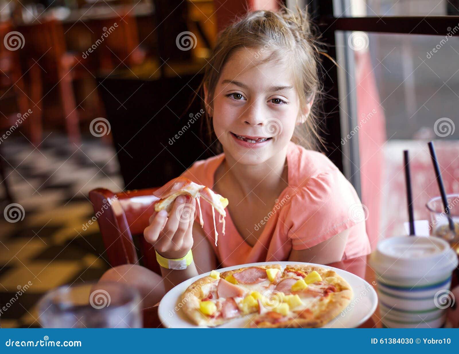 Śliczna mała dziewczynka je kawałek pizza w restauraci